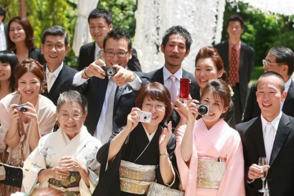 写真を撮る結婚式の参列ゲスト